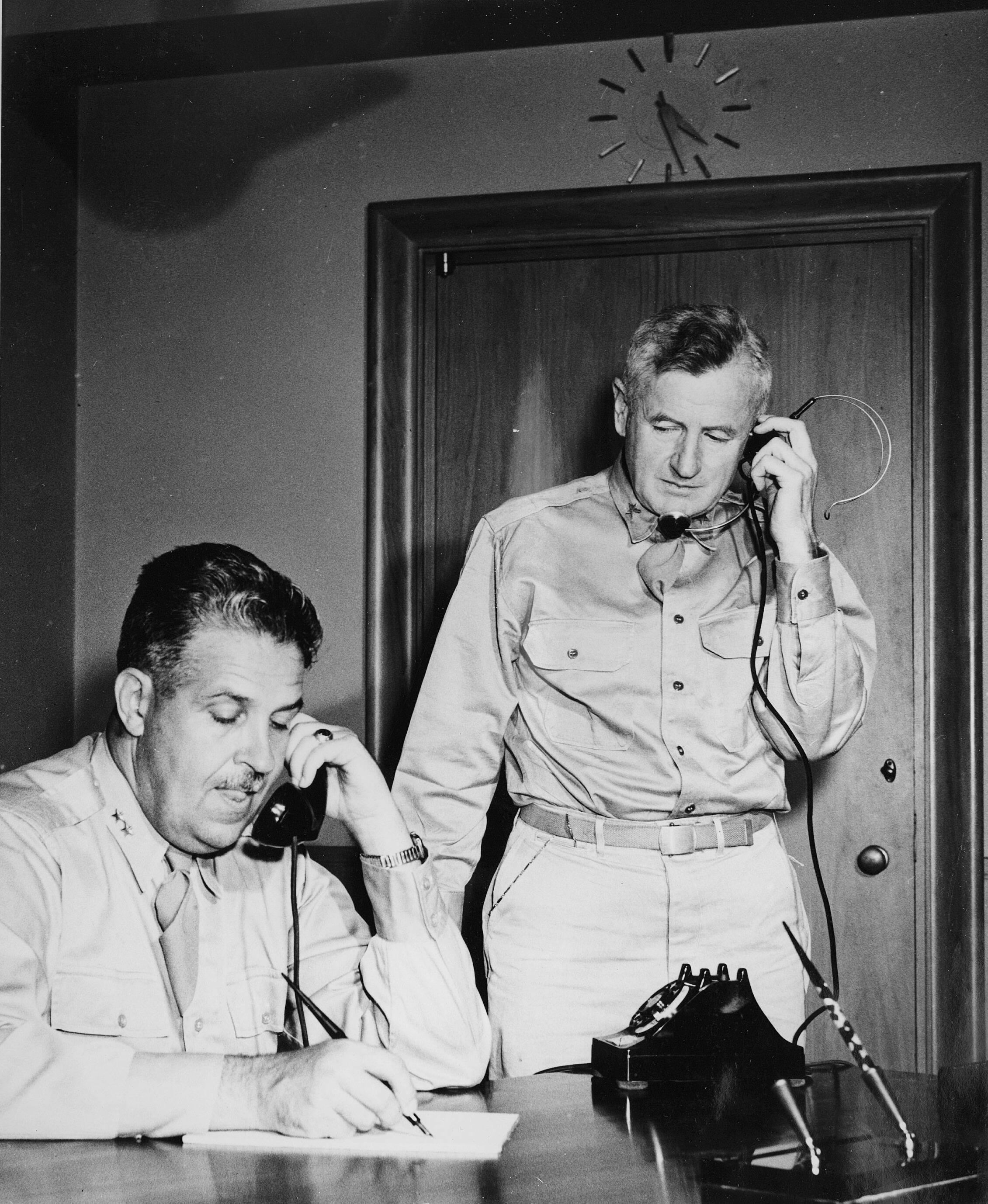 Two men in shirts and a ties. One is sitting at a desk and the other standing. Both are talking on telephones.