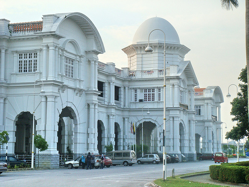 Closeup of the Ipoh station's station building facade, depicting its ornate construction and scale relative to parked road vehicles. Ipoh railway station.jpg