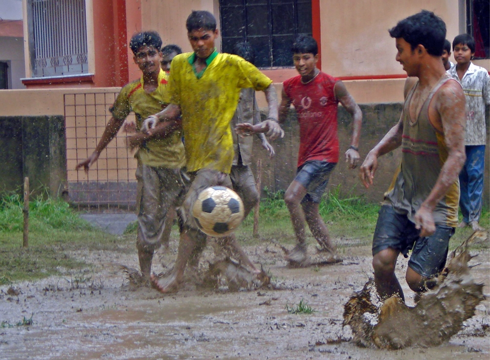 Football is a popular sport in Kolkata. Here amateur players enjoy a game in the rain.