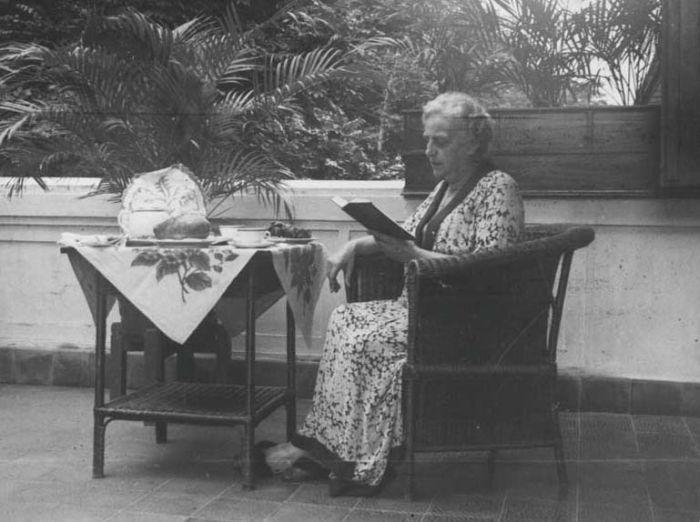 COLLECTIE TROPENMUSEUM Mevrouw Vattier - Kraane leest bij de theetafel Hotel des Indes Batavia TMnr 60018267