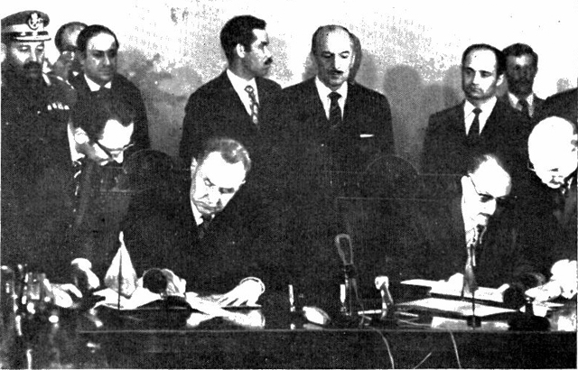 Two men signing an agreement, with other men standing behind them