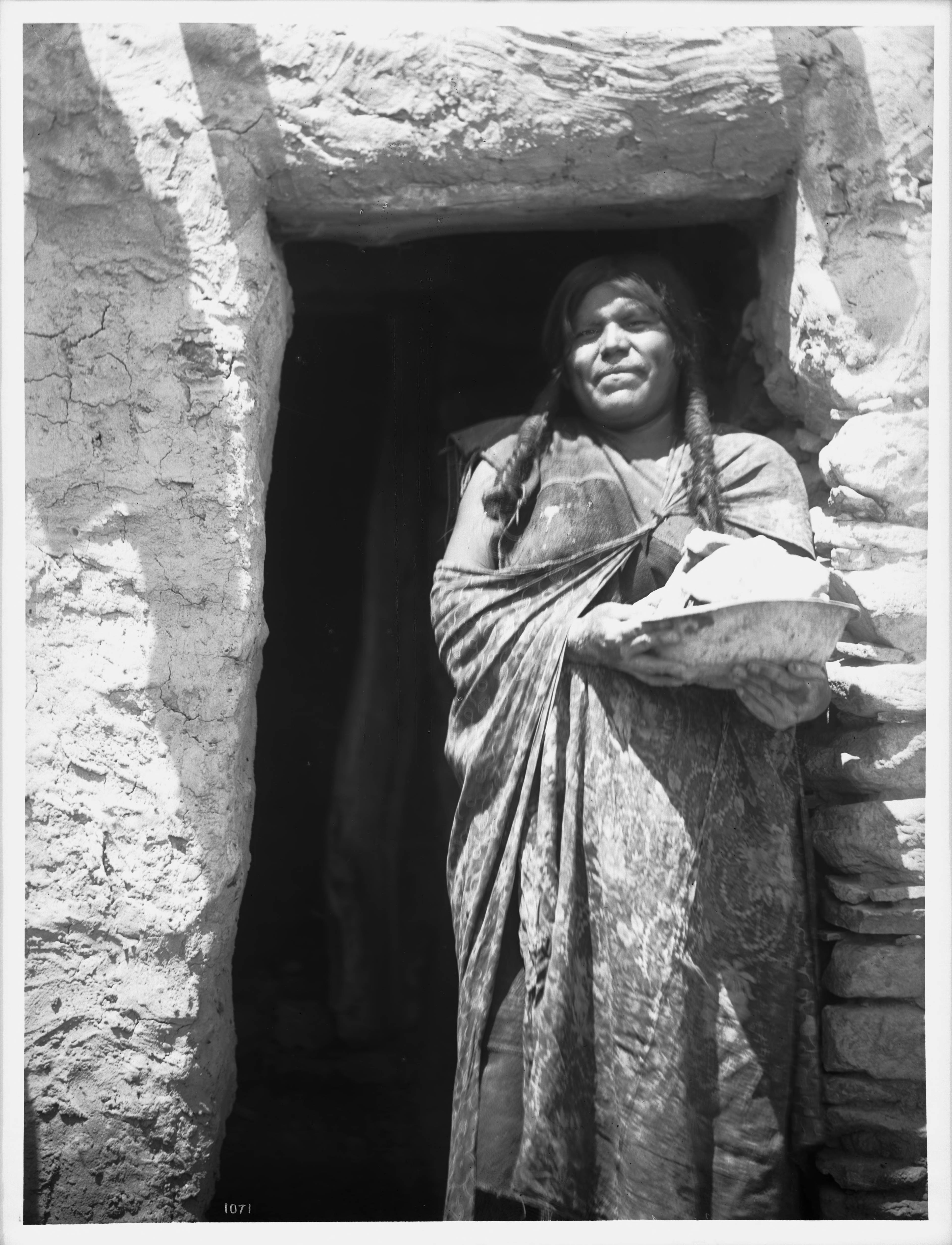 File:Hopi Indian woman holding a stone for house construction in the