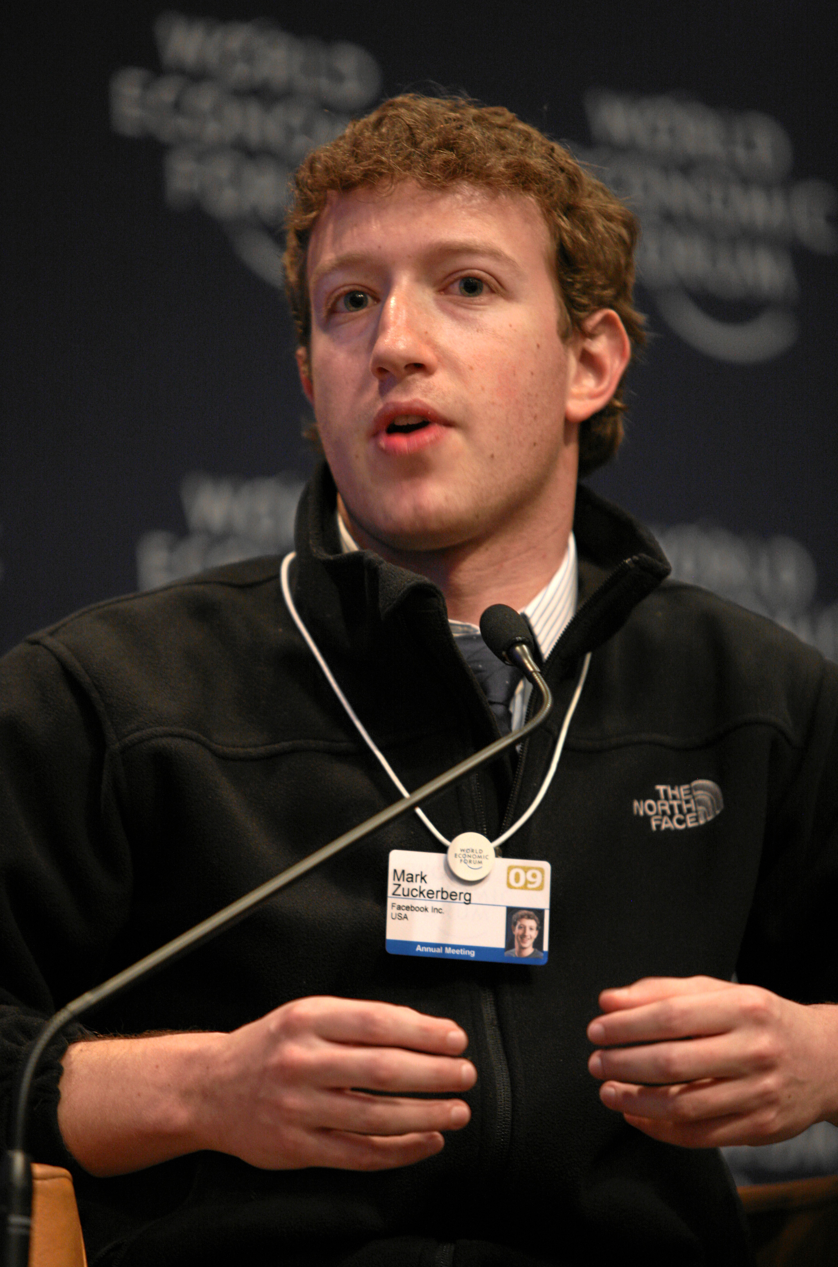 "Waist high portrait of man in his thirties, looking into the camera and gesturing with both hands, wearing a black pullover shirt that says ""The North Face"" and wearing identification on a white band hanging from his neck"