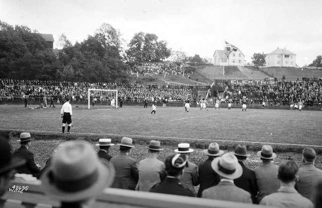 Et bilde i gråtoner hvor det i forgrunnen er tilskuere og i bakgrunnen en fotballbane hvorpå det spilles fotball