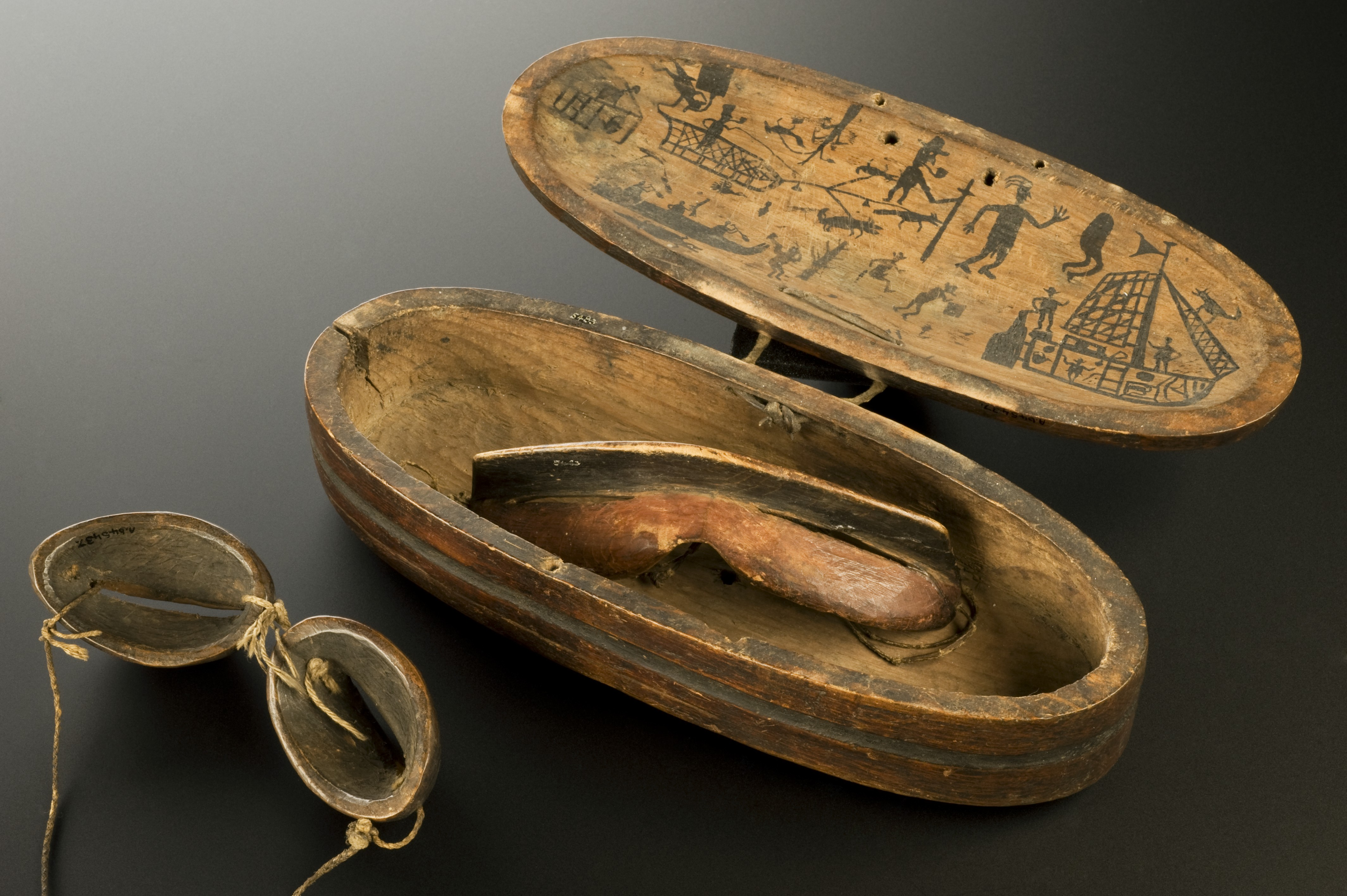 In the center, there's a wooden case with delicate drawings about hunting and ships. It holds a snow goggle, which has with very thin slits for the eyes. On the bottom left is another snow google, as seen from behind, with ropes mainting the pieces in place