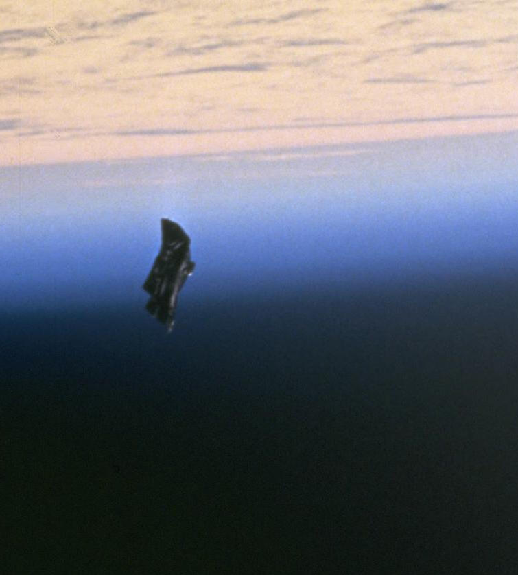 "1998 NASA photo of space debris,[1] an object believed by some conspiracy theorists to be an extraterrestrial satellite, the ""Black Knight."""