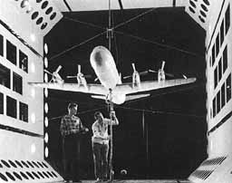 Two men testing a scale model airplane in a wind tunnel.