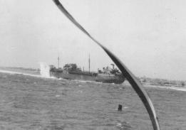 Photograph taken from USS Pivot (AM-276) in the Pacific in 1945 of an unknown Escambia class vessel being hit