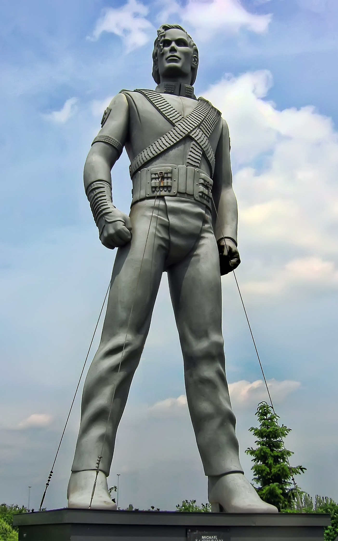 A silver colored statue of a male. The statue is placed standing up with its arms bent inward and both legs spaced apart. The statue's clothes have wrinkles and it is wearing heeled shoes. In the background, a tree and a light blue sky with multiple clouds can be seen.