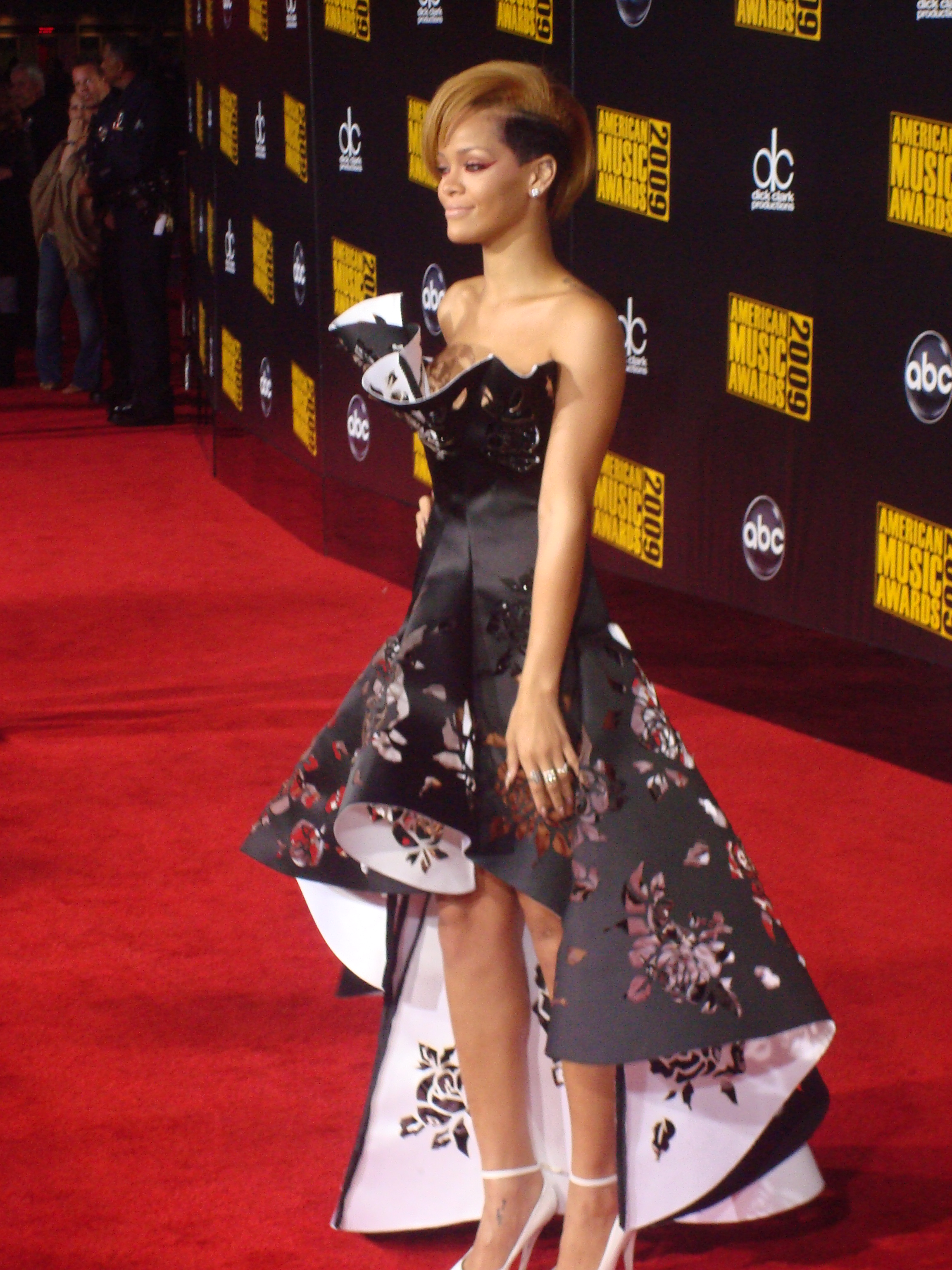 rihanna standing on a red carpet in an elaborate dress - Rihanna Lebenslauf