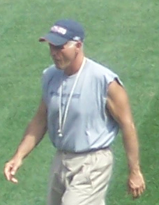Candid photograph of Scarnecchia walking on a football field wearing a grey sleeveless t-shirt and a blue baseball cap