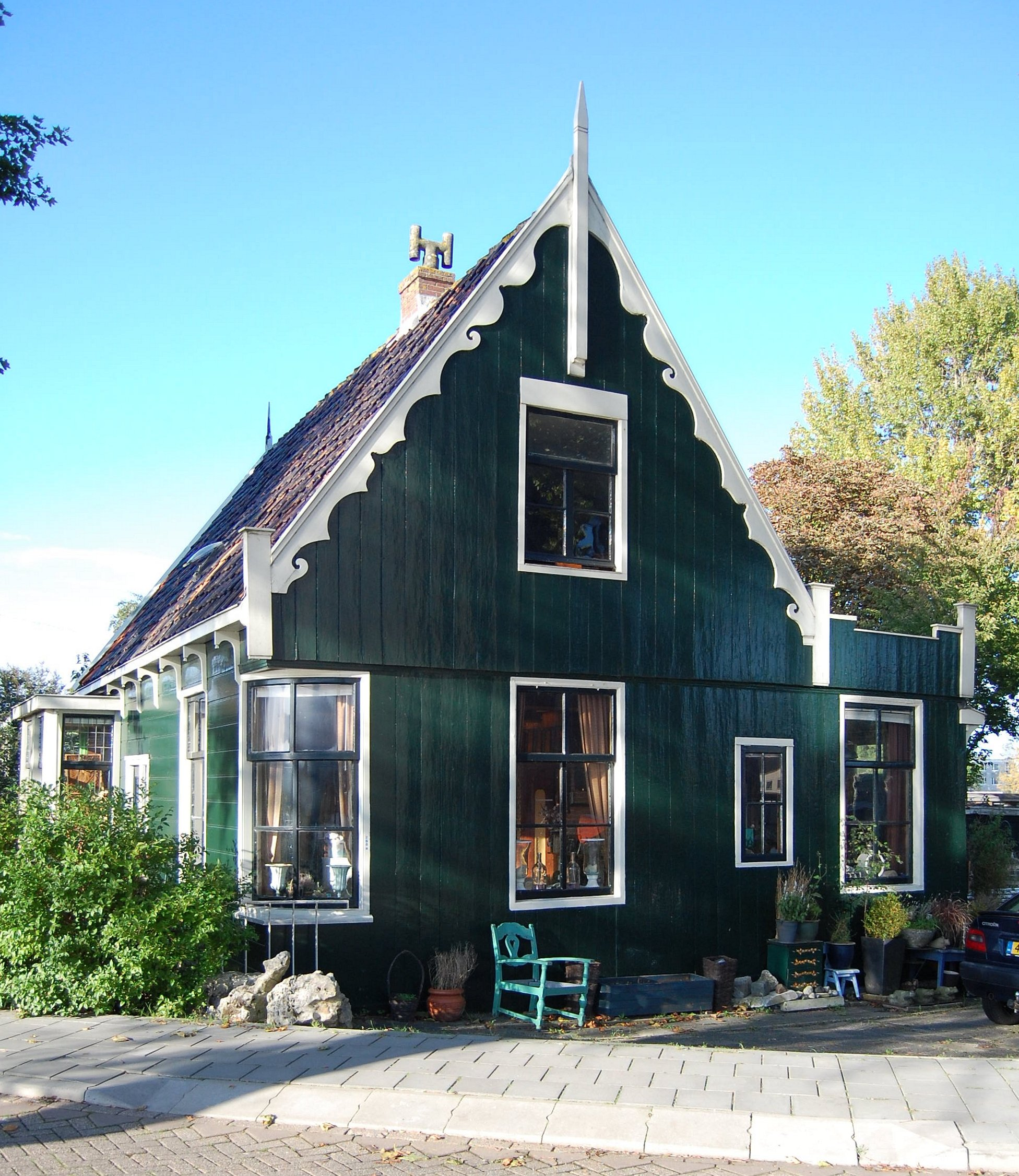 Houten huis met gebogen hoekvenster en een topgevel met uitgeschulpte windveren in zaandam for Hout huis