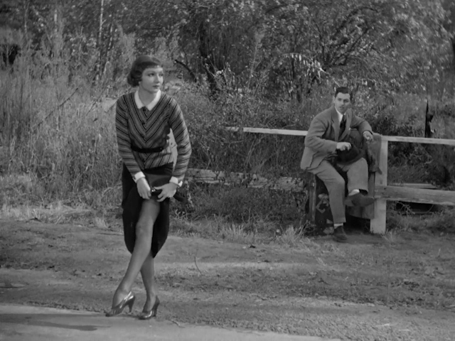 Claudette Colbert shows her shapely leg to stop a passing car