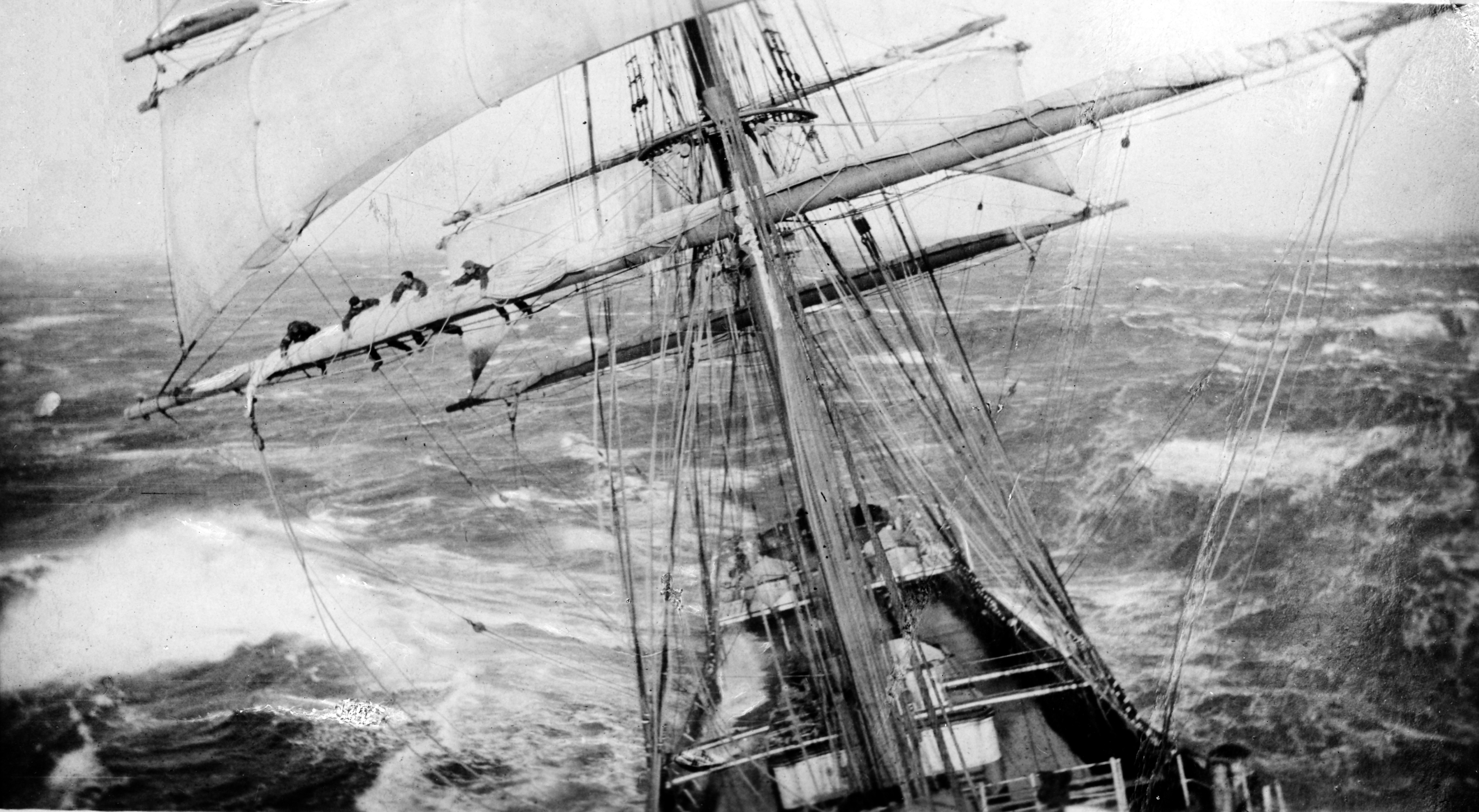 The full-rigged ship Garthsnaid in heavy seas, with men working in the rigging