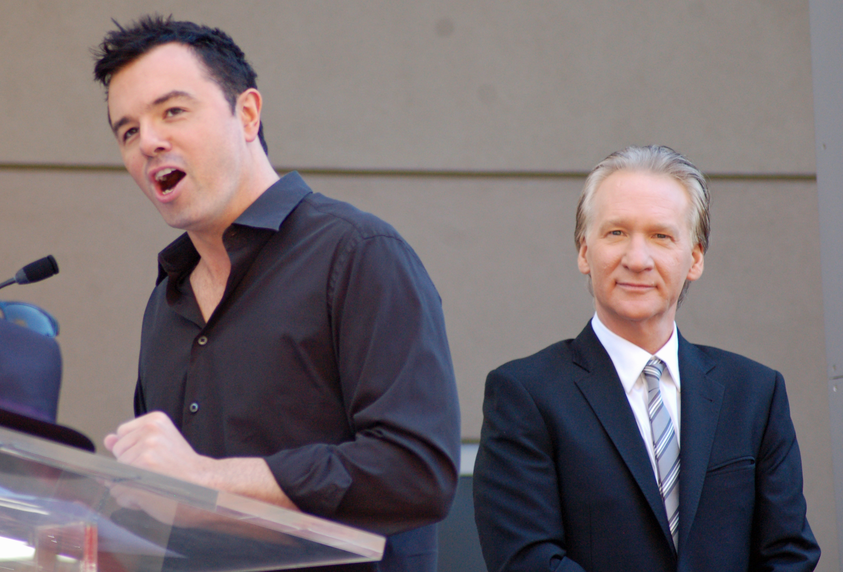 A man with black hair and slight stubble, wearing a black button-up shirt, speaking into a microphone. A man with gray hair, looking straight forward, and wearing suit, sits behind him.