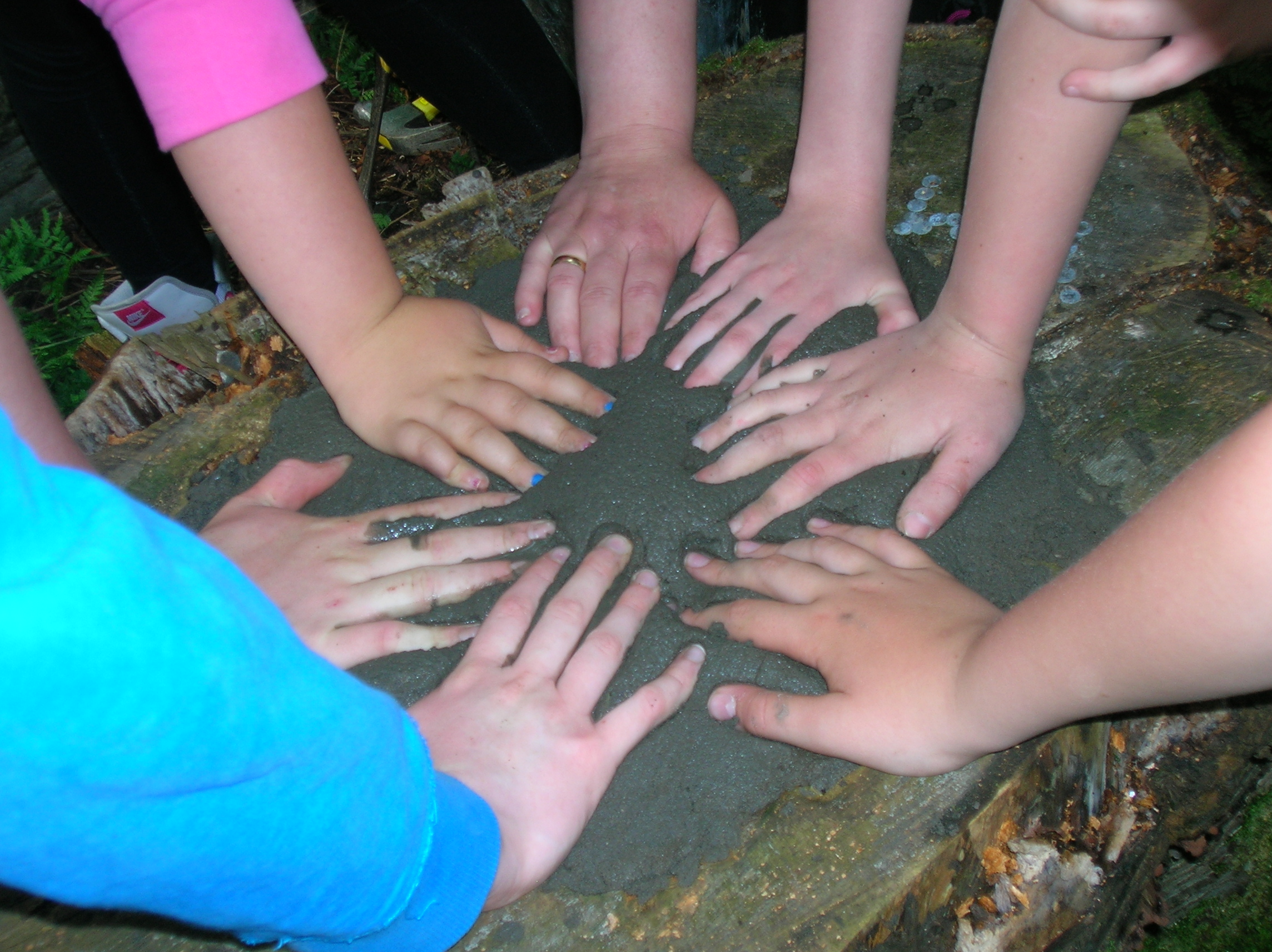 A circle of hands touching a rock.