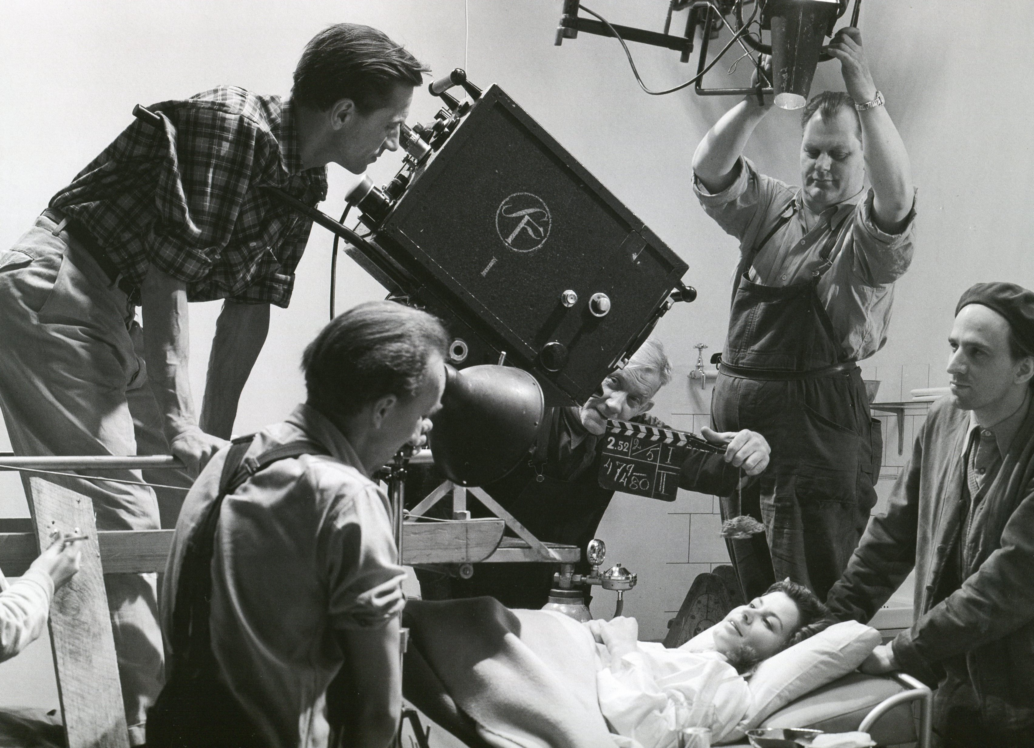 Cinematographer Gunnar Fischer (behind the camera) during the filming of Waiting Women, to the right of Ingmar Bergman and the bed Maj-Britt Nilsson.