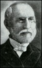 Head shot of balding gentleman with neatly trimmed white hair, moustache and beard, wearing glasses