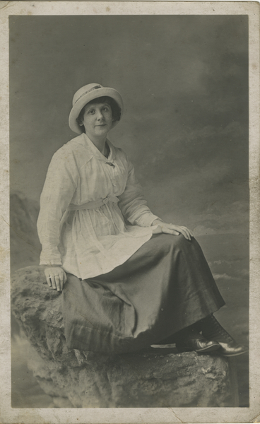 File:Photograph, black and white, studio portrait of young woman sitting on a rock with a backdrop of the sea. Wearing white long sleeved tunic worn over dark skirt with small brimmed hat and laced boots. (16026619915).jpg