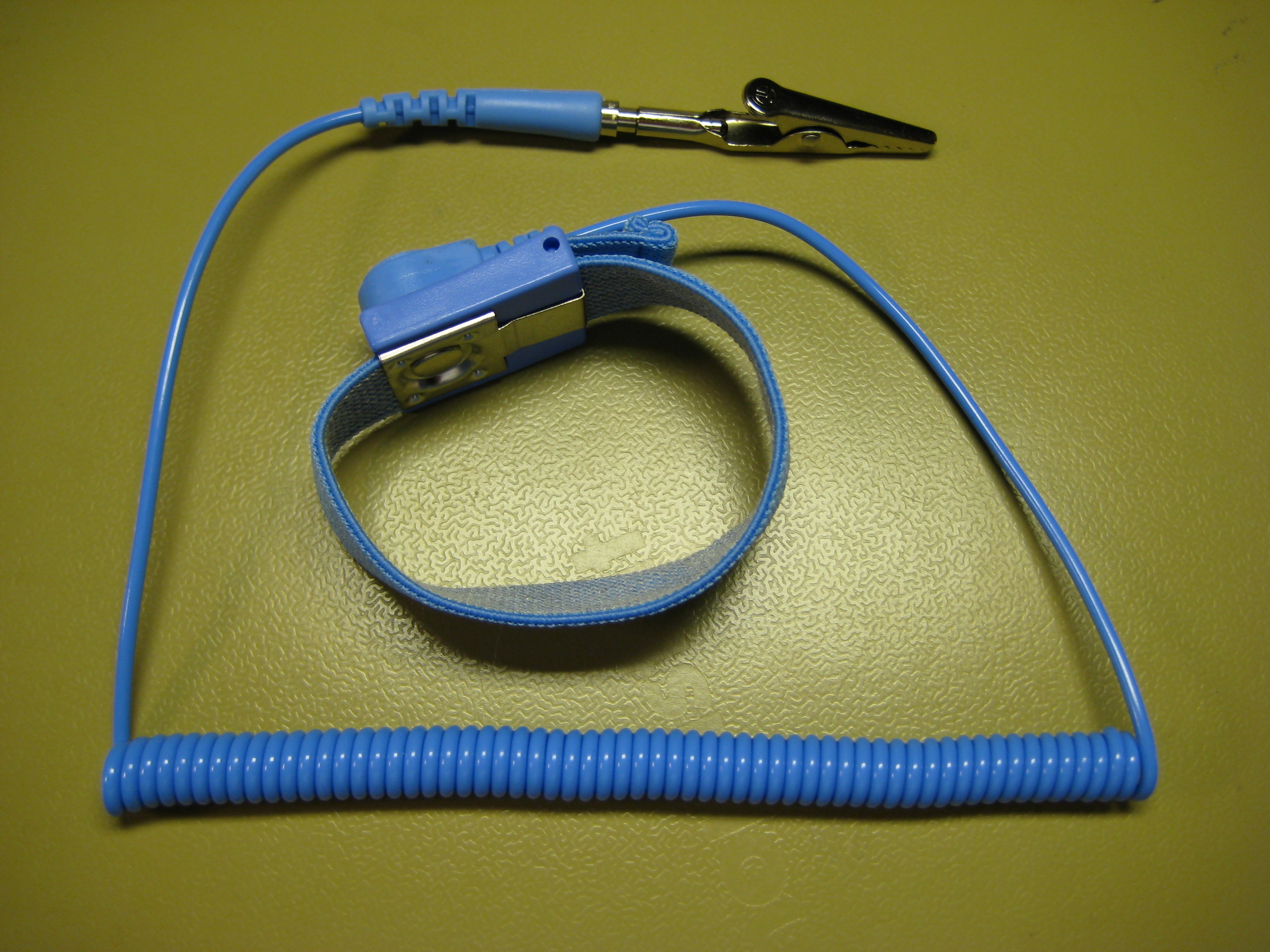 Blue Anti-Static Wrist Strap on Yellow Background With Curly Cord Leading to Alligator Clip