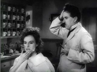 A black-and-white screenshot of a woman sitting in a chair. She is rubbing her face and a barber is standing at her right and is holding his head with his right hand. The two people are located in a barbershop.