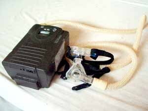 Oxygen therapy device with face mask lying on a bed.