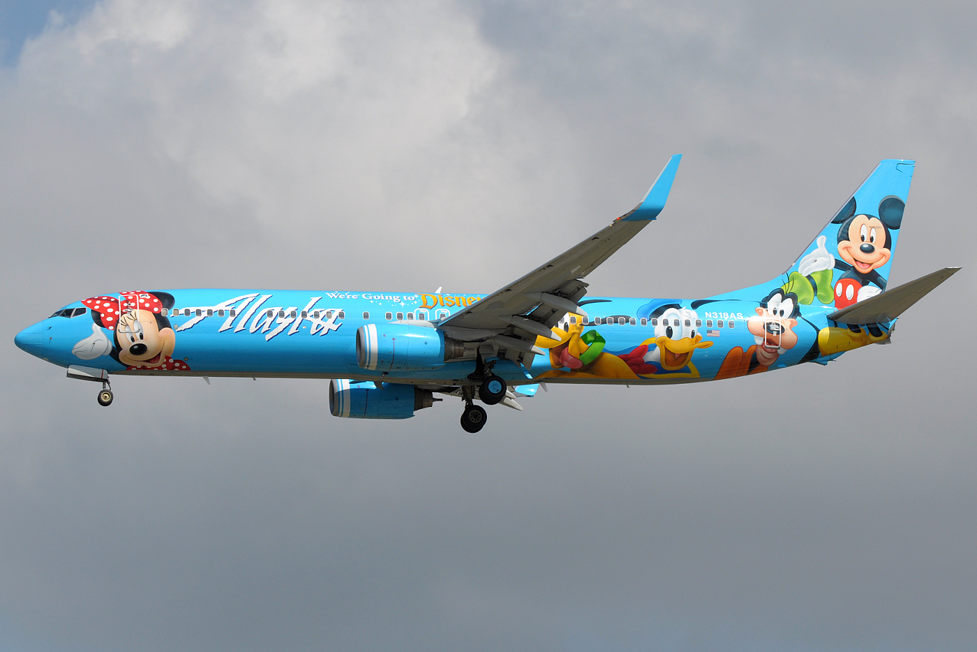 Left side view of a light blue aircraft adorned with Mickey Mouse and other Disney characters, with dark clouds in the background.