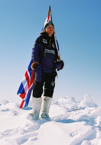 A figure standing on snow in dark clothing and white boots carries a British flag.