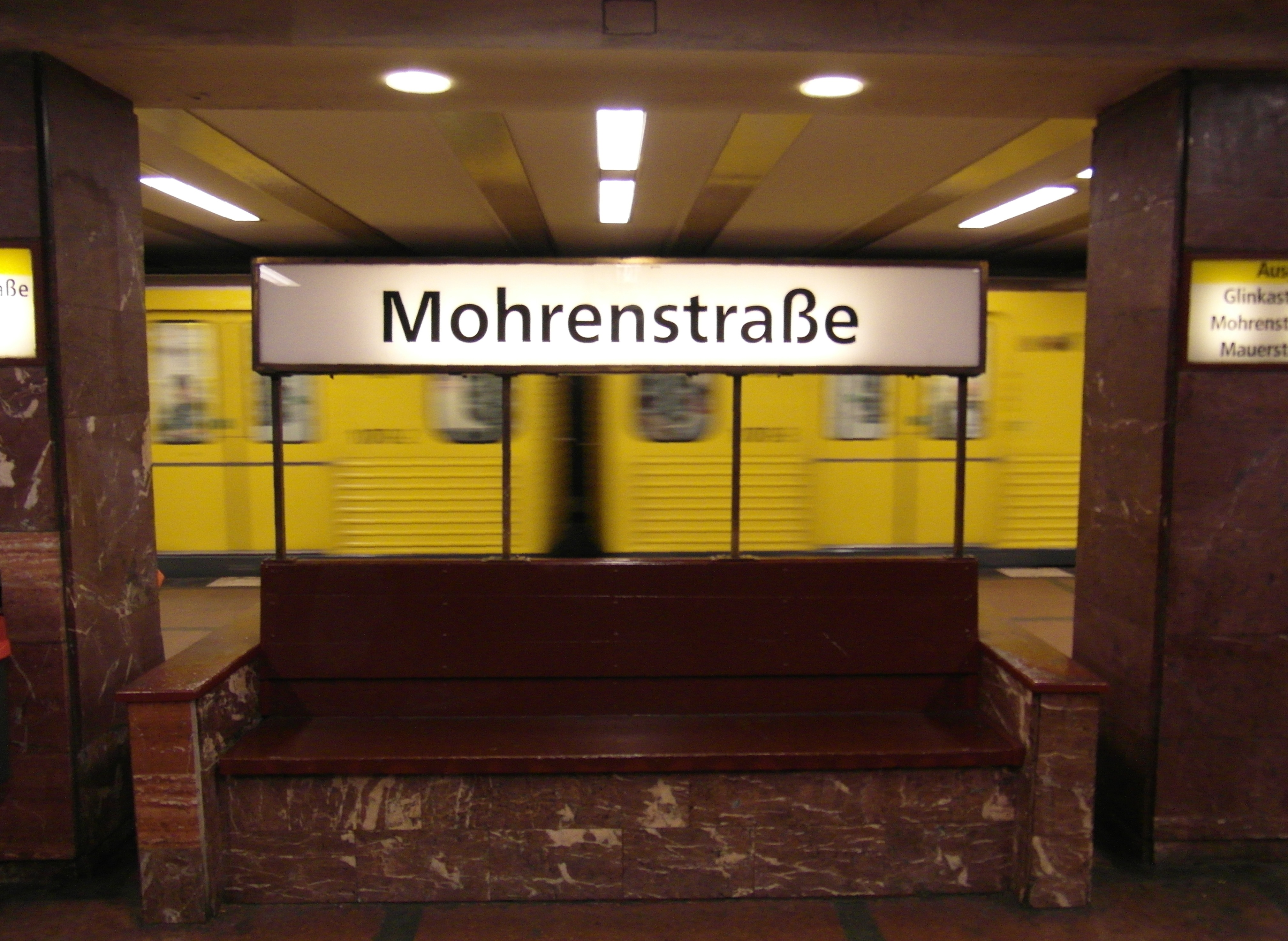 interior of U-Bahn station Mohrenstraße in Berlin showing a bench and sign in the foreground and a yellow subway train in motion in the background