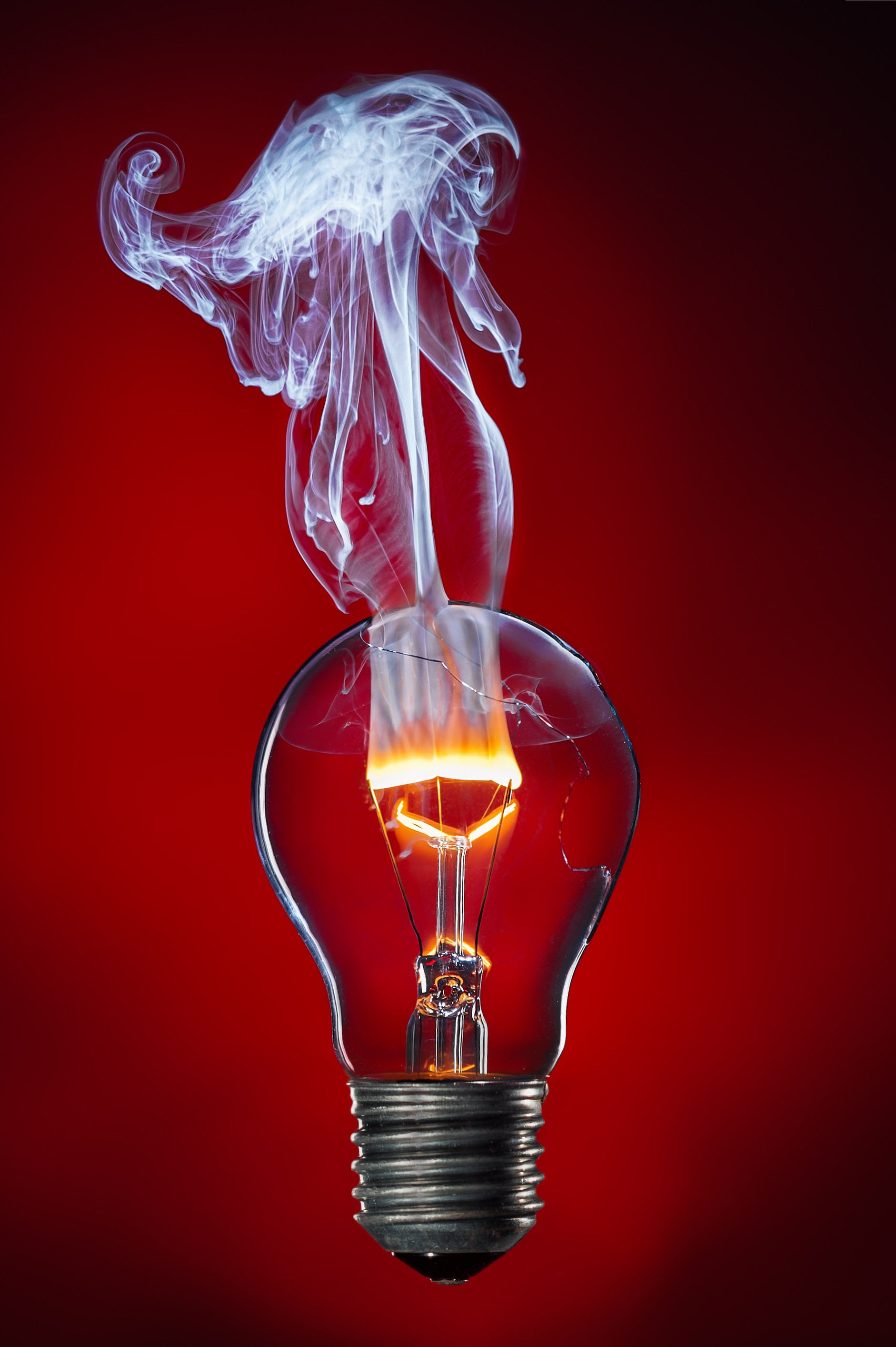 The tungsten filament burning with a flame in the light bulb.