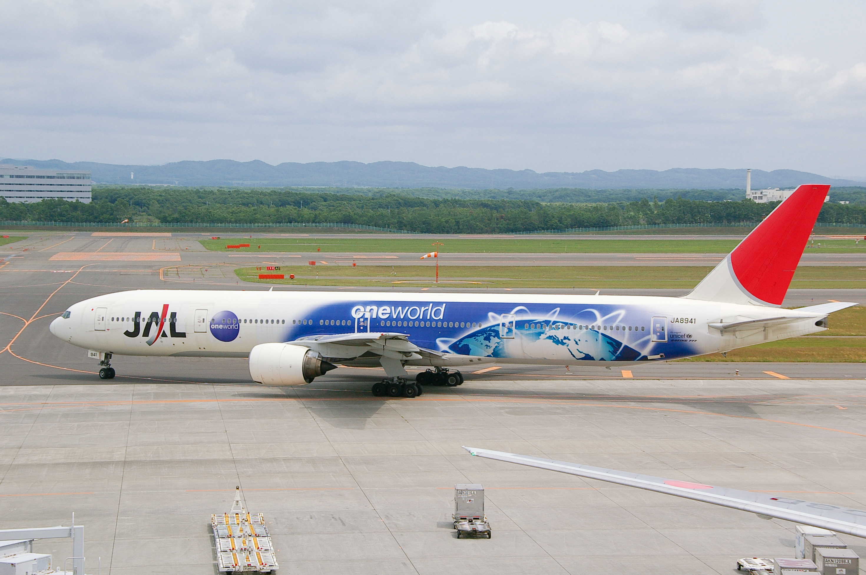 A Boeing 777–300 aircraft with special Oneworld livery taxiing from the tarmac on to the taxiway, with a mountain view on the background