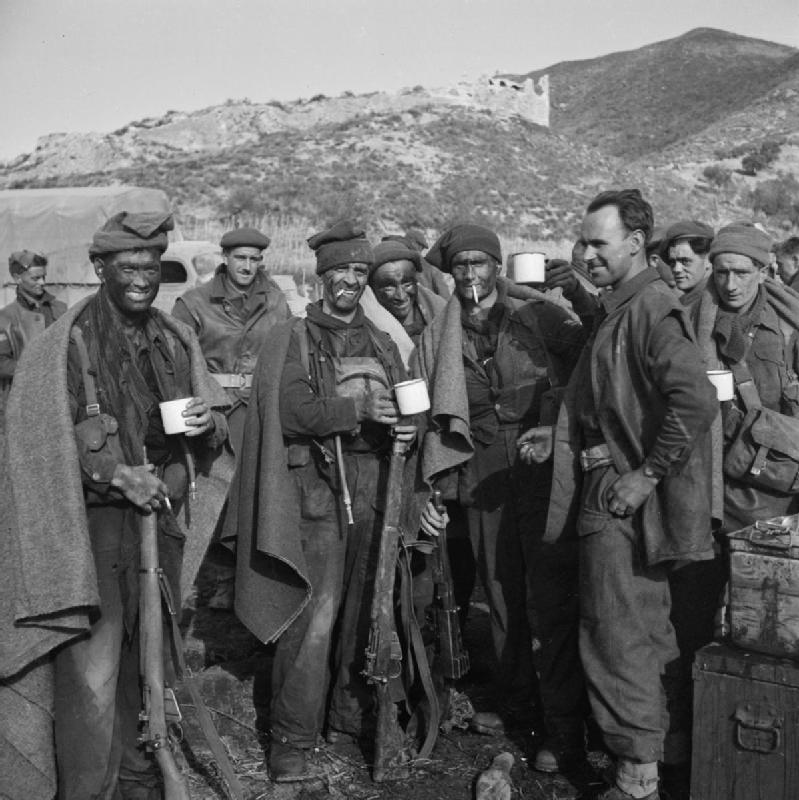 group of commandos with blackened faces drinking from cups. They have blankets around their shoulders and in the background are mountains