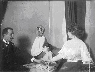 A photograph of the medium Linda Gazzera with a doll as fake ectoplasm. Seance Doll.jpg