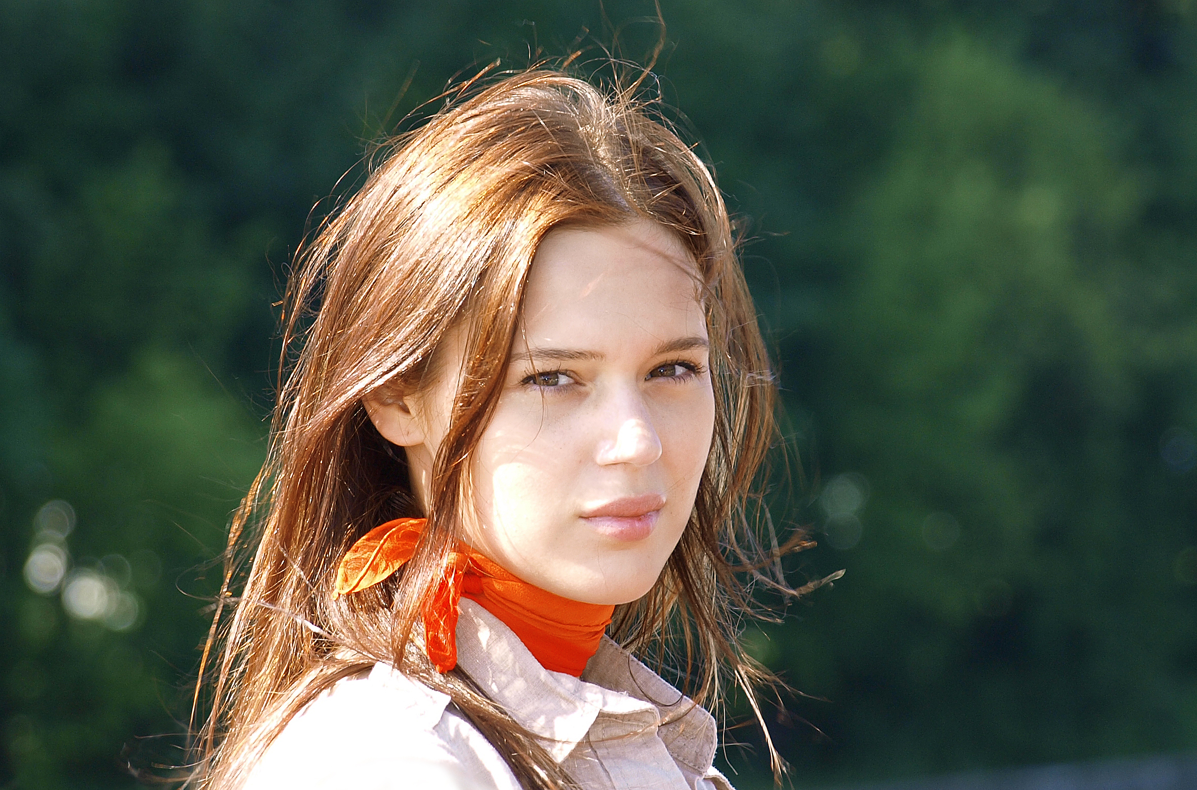 Woman_with_a_light_brown_blouse_and_a_red_scarf.jpg