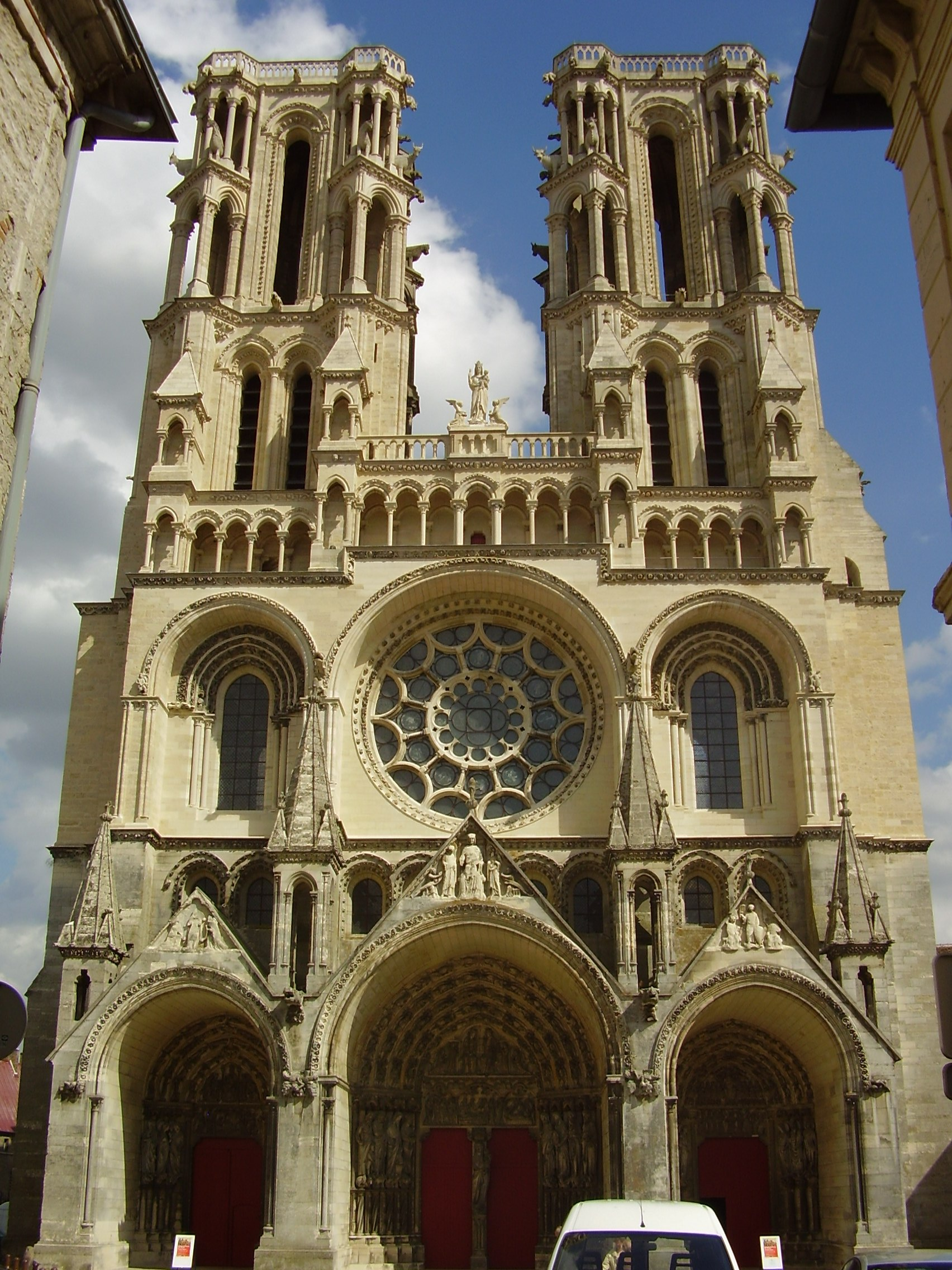 An image of the front facade of the Notre-Dame de Laon Cathedral taken in July 2009 on a sunny day. The Cathedral is a pale yellow stone colour on a bright sky blue background.