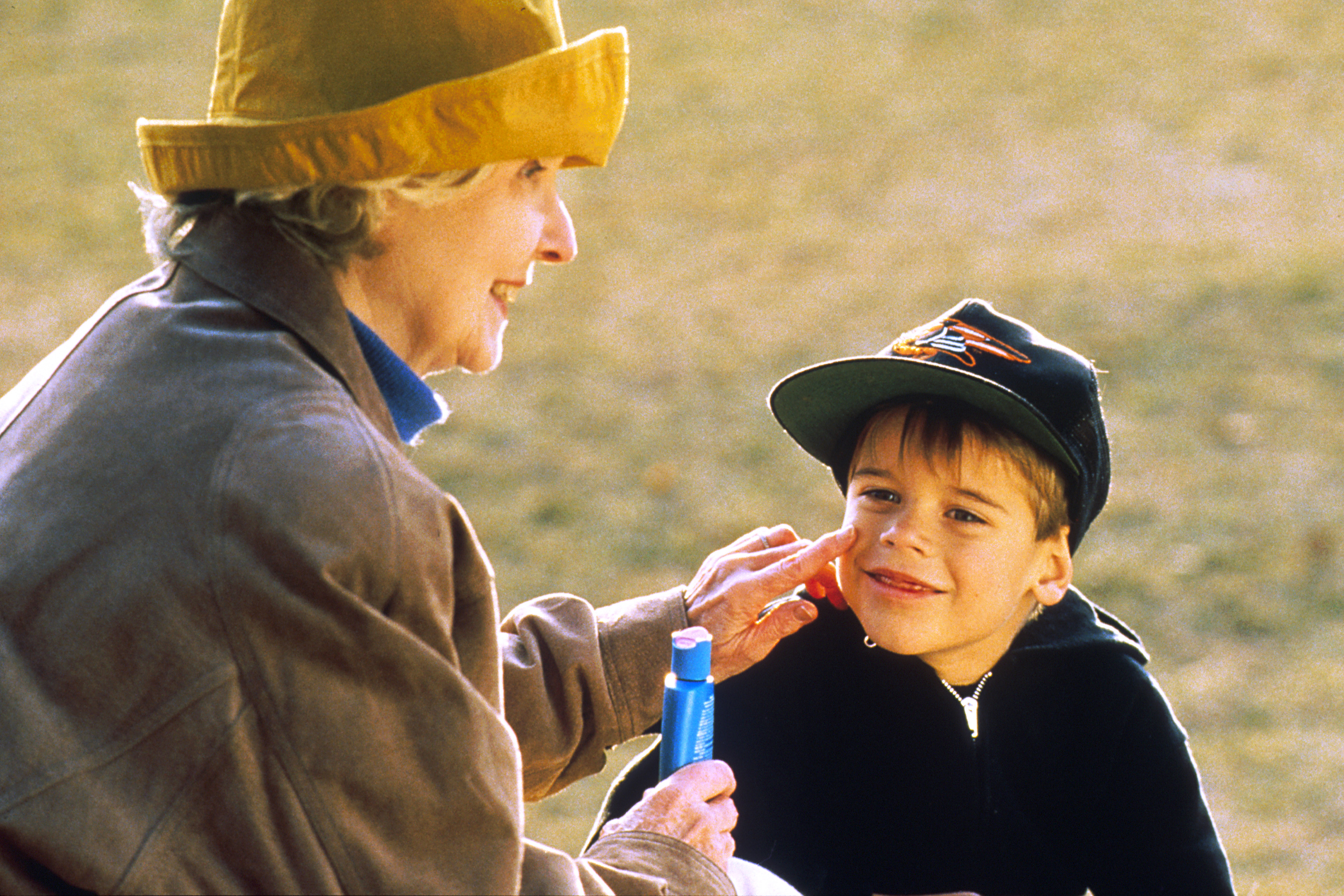 An older Caucasian women applying sunscreen to young Caucasian child.
