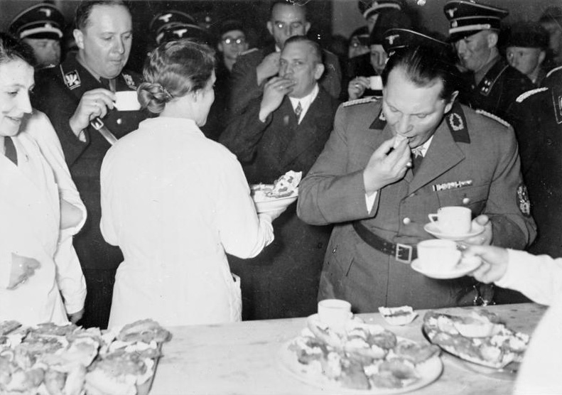 """Prime Minister of the fascist Nazi Reich, Hermann Goering, kicks off Green Week with the """"Frugal Housewife"""" program and a spread of raw food"""