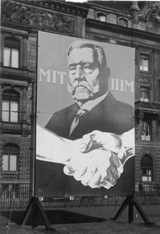 """Campaign poster depicting Hindenberg and two hands in a handshake. A large caption reads, """"Mit ihm"""" (""""With him"""")."""