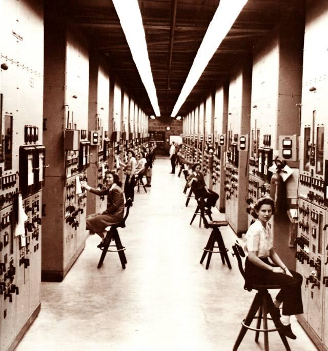 Pannelli di controllo e operatori davanti agli enormi calcolatori presso il Complesso Y-12 a Oak Ridge, Tennessee.