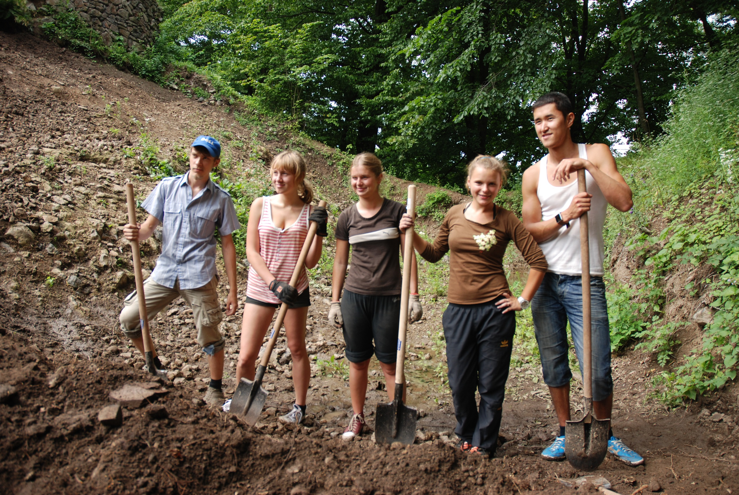 Young people standing with shovels.