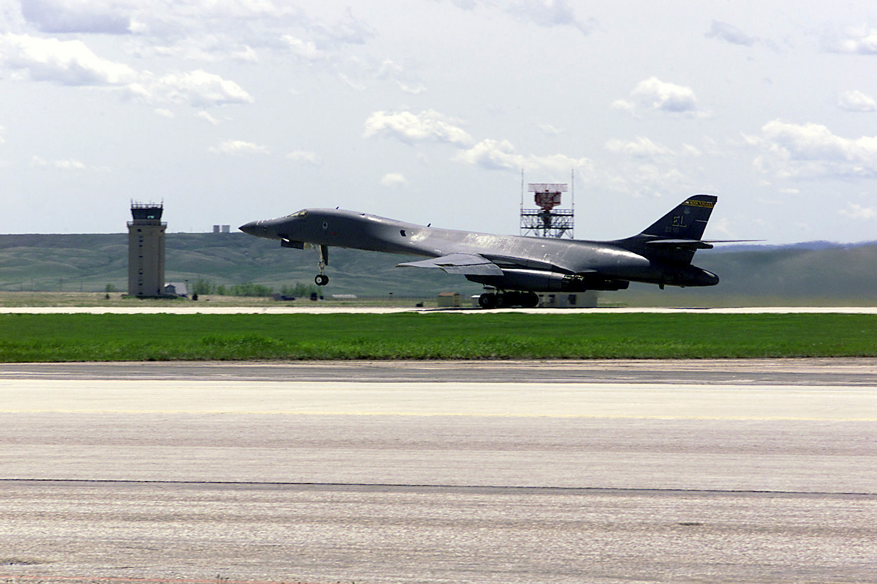 A B-1B Lancer takes off from Ellsworth AFB in front of the control tower and radar.
