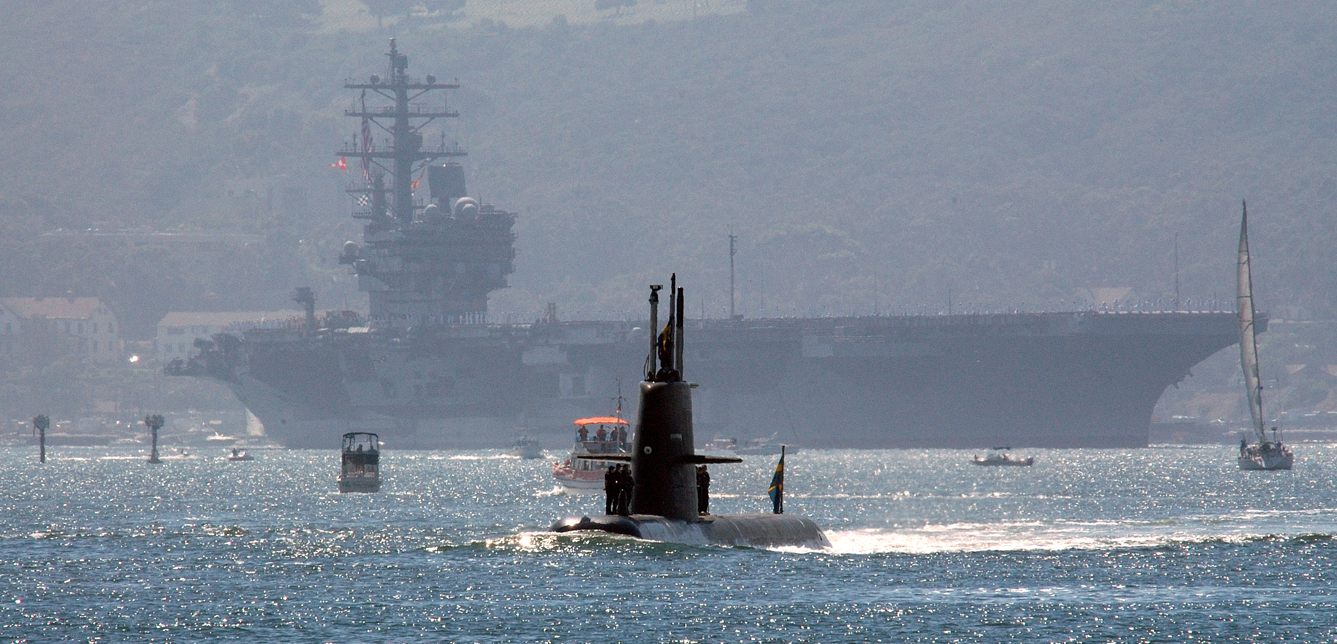 Swedish Stirling engine-powered attack submarine HMS Gotland transits through San Diego Harbor with the Nimitz-class aircraft carrier USS Ronald Reagan