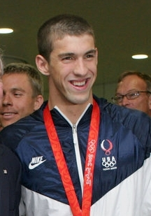 Grinning young man with very short black hair with a gold medal hung around his neck on a red ribbon. He is wearing a white and blue tracksuit designated as the uniform of the United States and someone else's hand is waving an American flag in front of his torso. Two men are standing behind him.