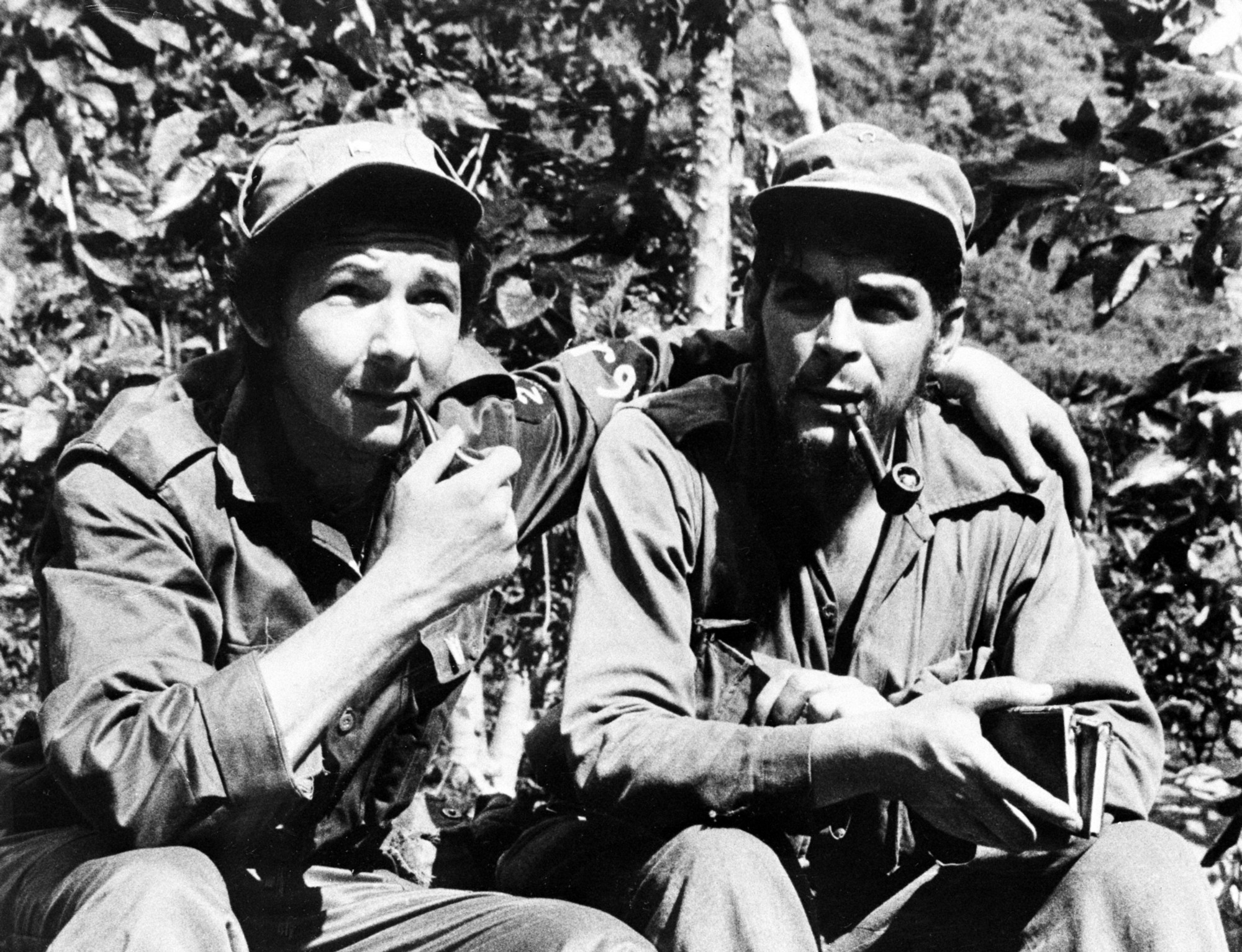 "Raúl Castro (left), with his arm around his second-in-command, Ernesto ""Che"" Guevara, in their Sierra de Cristal mountain stronghold in Oriente Province, Cuba, in 1958"