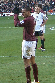 Thierry Henry, wearing gloves and a redcurrant football shirt applauds the crowd. A stand full with people and man wearing a football shirt are visible in the background.