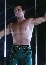 Frame from a film showing the torso of a bare-chested man standing on a circus trapeze; the man's arms are extended outwards from his body, and he's facing somewhat left of the camera.