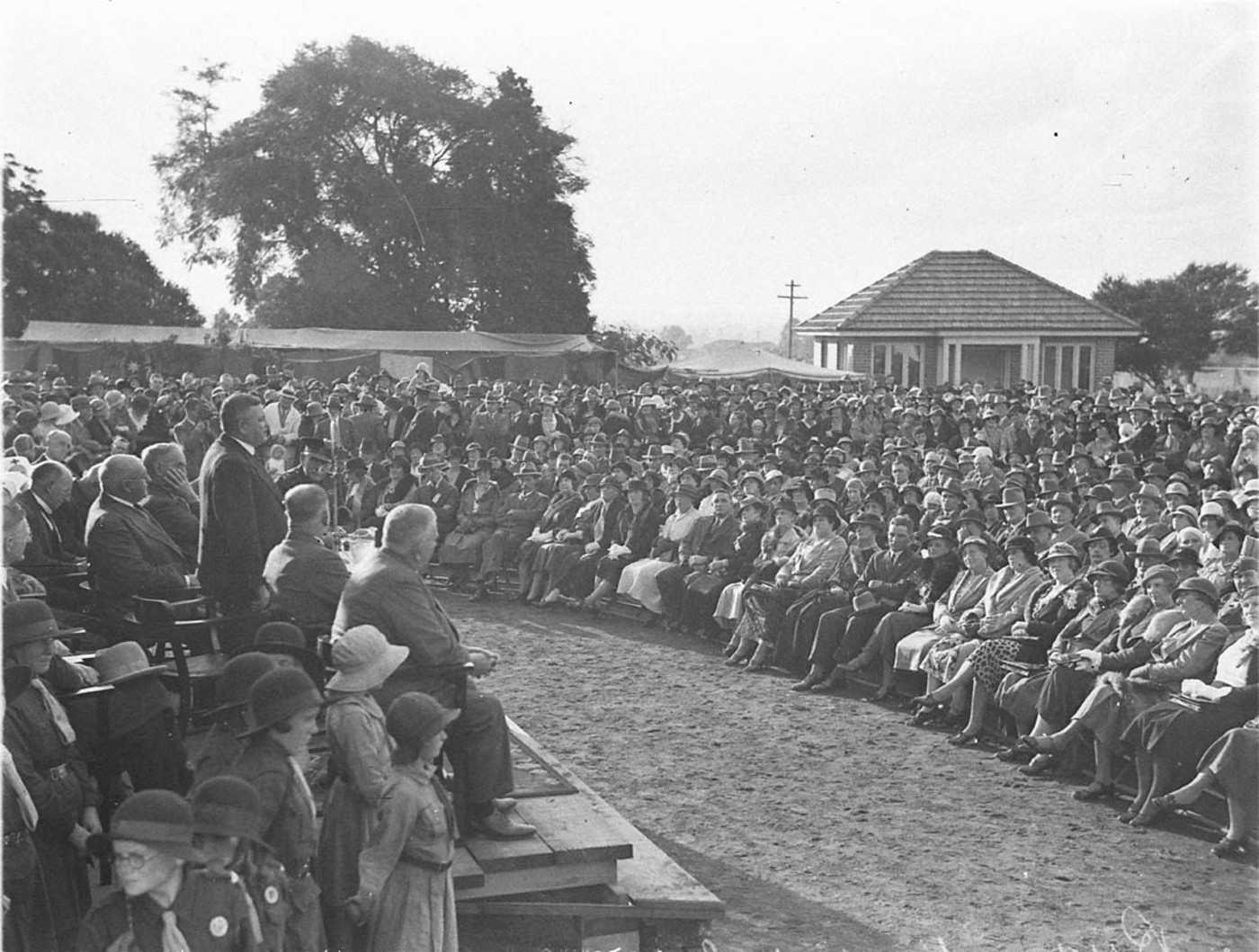 Black-and-white photo of a seated crowed arranged in a semicircle around an outside dais with a number of speakers