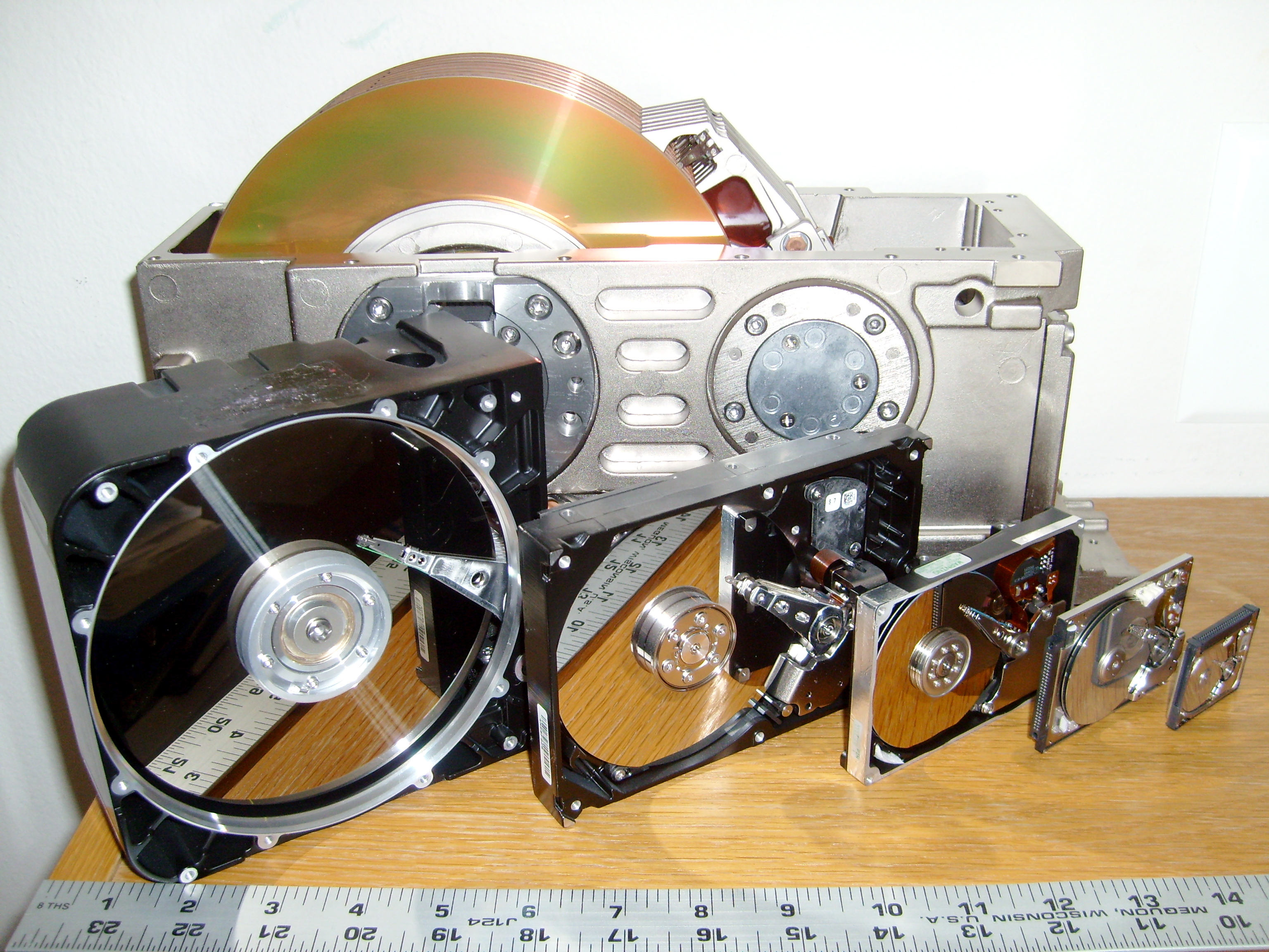 Six hard drives with 8 , 5.25 , 3.5 , 2.5 , 1.8 , and 1 hard disks with a ruler to show the length of platters and read-write heads.