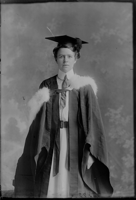 Three quarter length portrait of Miss Kate Violet Edgerley in academic cap and gown standing