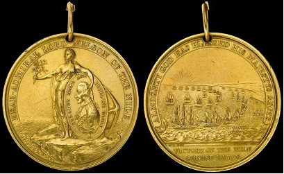 Battle of the Nile Medal in Gold. Normally worn from a wide blue ribbon. Grades: 4, awarded by rank. Gold: awarded to Nelson and his captains. Silver: awarded to lieutenants and warrant officers. Copper-Gilt: awarded to petty officers. Bronzed copper: awarded to ratings, marines, etc. Battle of the Nile Medal Gold.png